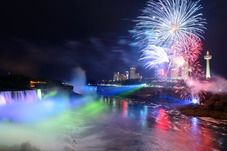 niagara: Niagara Falls lit at night by colorful lights with fireworks