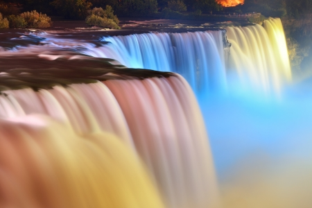 niagara river: Niagara Falls lit at night by colorful lights