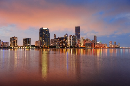 with reflection: Miami city skyline panorama at dusk with urban skyscrapers over sea with reflection Stock Photo
