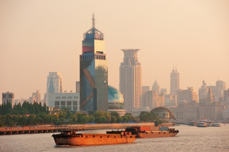 pudong district: Boat in Huangpu River with Shanghai urban architecture at sunset