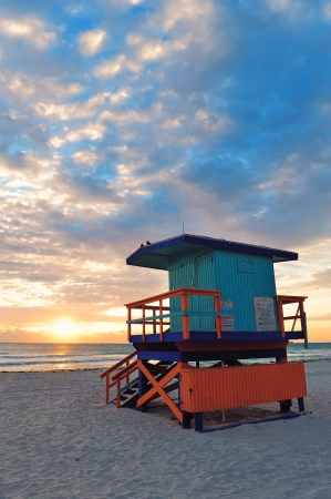 Miami South Beach sunrise with lifeguard tower and coastline with colorful cloud and blue sky. photo