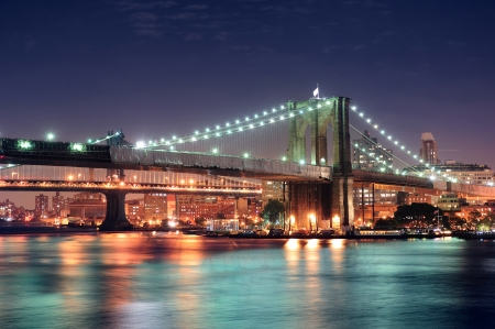 east river: Brooklyn Bridge over East River at night in New York City Manhattan with lights and reflections  Stock Photo
