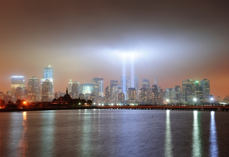 New York City Manhattan downtown skyline at night from Liberty Park with light beams in memory of September 11 viewed from New Jersey waterfront