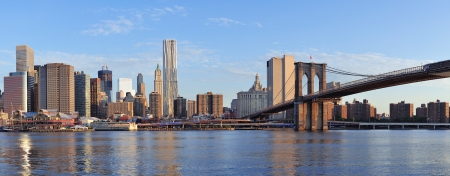 manhattan: Brooklyn Bridge with lower Manhattan skyline panorama in the morning with cloud and river reflection over East River in New York City