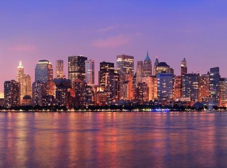 허드슨 강 파노라마를 통해 조명 고층 빌딩으로 황혼 뉴욕시 맨해튼 시내의 스카이 라인