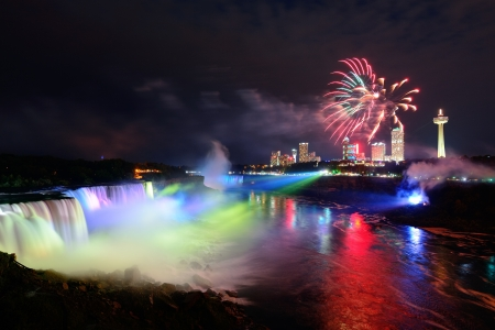niagara river: Niagara Falls lit at night by colorful lights with fireworks