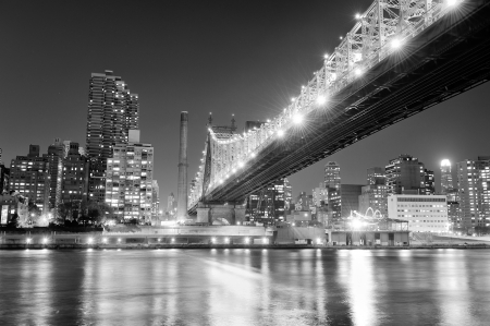 Queensboro Bridge over New York City East River black and white at night with river reflections and midtown Manhattan skyline illuminated.  Stock Photo - 16383363