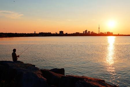 Toronto sunrise silhouette over lake with man fishing. Stock Photo - 16385820