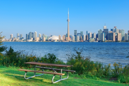 building cn tower: Toronto skyline in the day over lake with urban architecture viewed from park