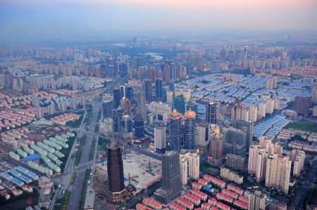Shanghai aerial view at sunset with urban skyscrapers over river photo