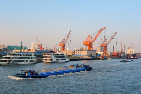 Boat in Huangpu River with Shanghai urban architecture and cargo crane  photo