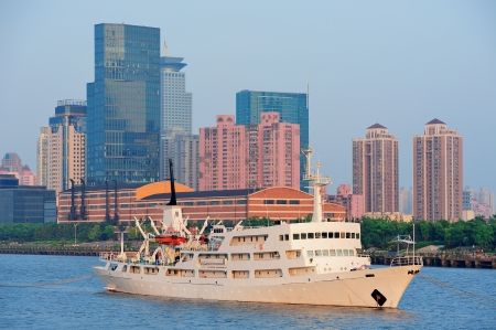 Boat in Huangpu River with Shanghai urban architecture photo