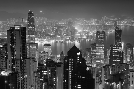 Hong Kong city skyline at night with Victoria Harbor and skyscrapers illuminated by lights over water viewed from mountain top in black and white. photo