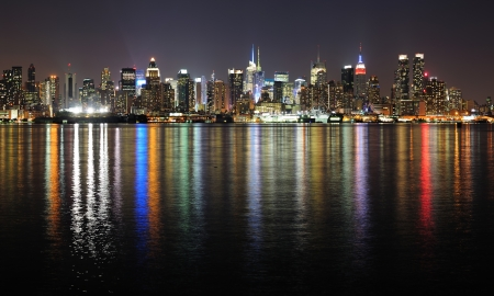 weehawken: New York City Manhattan midtown skyline panorama at night with lights reflection over Hudson River.