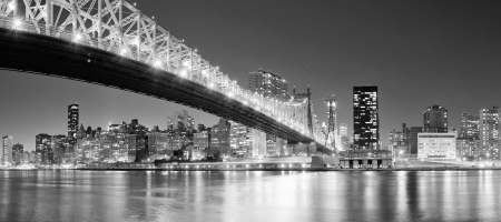 Queensboro Bridge over New York City East River black and white at night with river reflections and midtown Manhattan skyline illuminated   photo