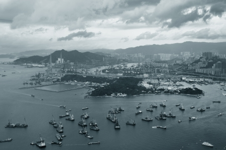 Victoria Harbor aerial view and skyline in Hong Kong with urban skyscrapers and boats in black and white. photo