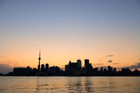 Toronto city skyline silhouette at sunset over lake with urban skyscrapers. Stock Photo - 17398112
