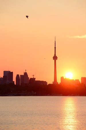 Toronto sunrise silhouette over lake with red tone. photo