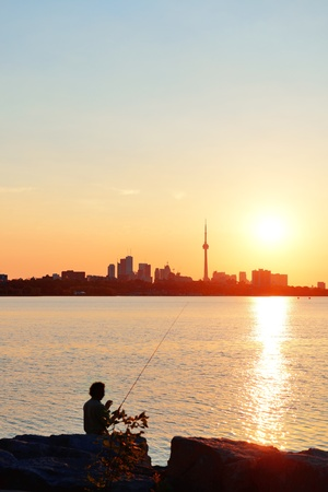 Toronto sunrise silhouette over lake with man fishing. Stock Photo - 17398828