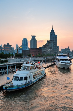 huangpu: Boat in Huangpu River with Shanghai urban architecture at sunset