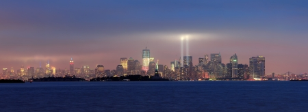 11: New York City Manhattan downtown skyline panorama at night with statue of liberty and light beams in memory of September 11 viewed from New Jersey waterfront.