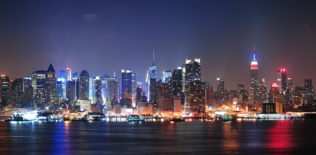 new york night: New York City Manhattan midtown skyline at night with skyscrapers lit over Hudson River with reflections.