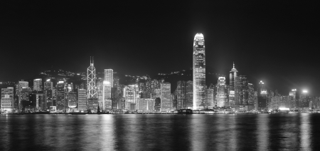 hong kong people: Hong Kong city skyline at night over Victoria Harbor with clear sky and urban skyscrapers.