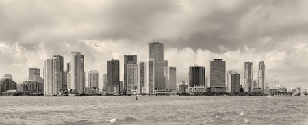 Miami skyline panorama in black and white in the day with urban skyscrapers and cloudy sky over sea  photo