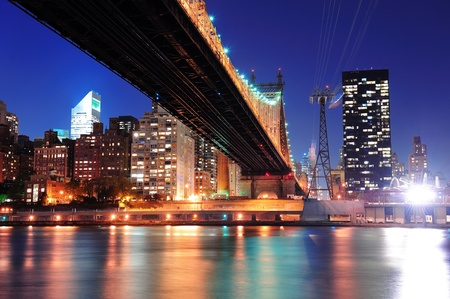 queensboro bridge: Queensboro Bridge over New York City East River at sunset with river reflections and midtown Manhattan skyline illuminated.