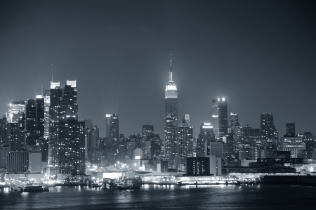 hudson river: New York City Manhattan midtown skyline black and white at night with skyscrapers lit over Hudson River with reflections.