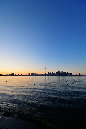 Toronto sunset silhouette at dusk over lake with urban architecture. photo