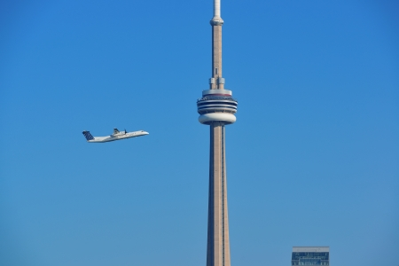 buit in: TORONTO, CANADA - JULY 2: CN Tower with airplane on July 2, 2012 in Toronto. Buit in 1976 as the unique landmark of Toronto, it was worlds tallest tower for 34 years