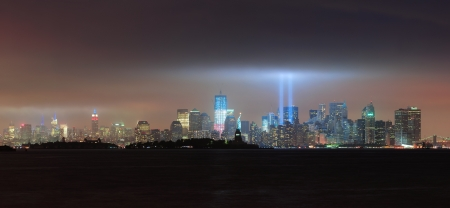 New York City Manhattan downtown skyline panorama at night with statue of liberty and light beams in memory of September 11 viewed from New Jersey waterfront. photo