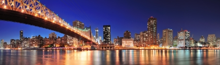 new york city: Queensboro Bridge over New York City East River at sunset with river reflections and midtown Manhattan skyline illuminated.