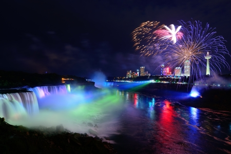 niagara falls: Niagara Falls lit at night by colorful lights with fireworks