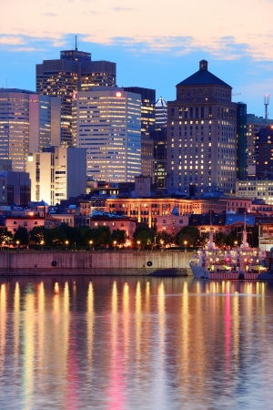 Montreal over river at sunset with city lights and urban buildings photo