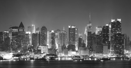 over black: New York City Manhattan midtown skyline black and white at night with skyscrapers lit over Hudson River with reflections