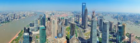 pudong district: Shanghai city aerial view panorama with urban architecture over river and blue sky in the day