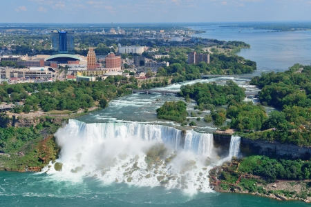 Niagara Falls closeup in the day over river with buildings photo
