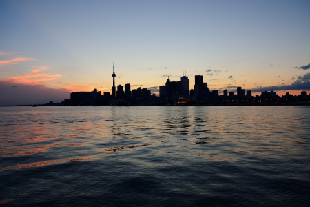 Toronto city skyline silhouette at sunset over lake with urban skyscrapers. Stock Photo - 18038461