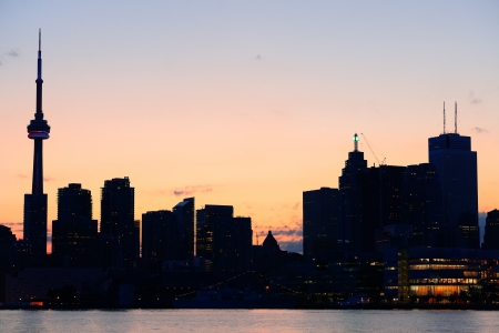 Toronto city skyline silhouette at sunset over lake with urban skyscrapers. Stock Photo - 18041198