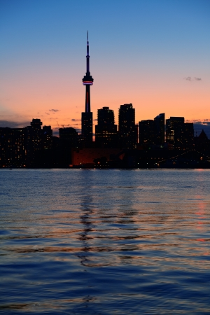 Toronto city skyline silhouette at sunset over lake with urban skyscrapers. Stock Photo - 18041755
