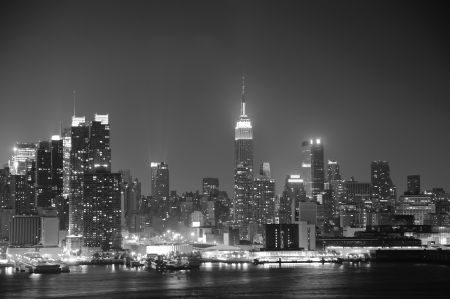 new york city times square: New York City Manhattan midtown skyline black and white at night with skyscrapers lit over Hudson River with reflections.