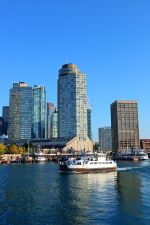 Toronto skyline in the day over lake with urban architecture and boat.