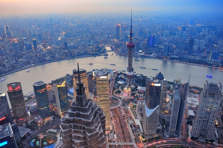 pudong district: Shanghai aerial view at sunset with urban skyscrapers over river