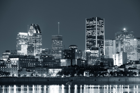 Montreal over river at dusk with city lights and urban buildings in black and white photo