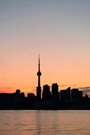 Toronto city skyline silhouette at sunset over lake with urban skyscrapers. photo