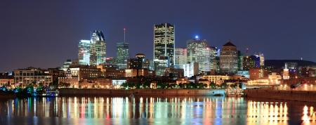 Montreal over river panorama at dusk with city lights and urban buildings Stock Photo