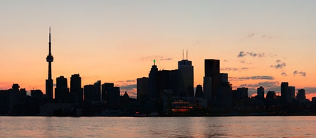 Toronto city skyline silhouette panorama at sunset over lake with urban skyscrapers. photo