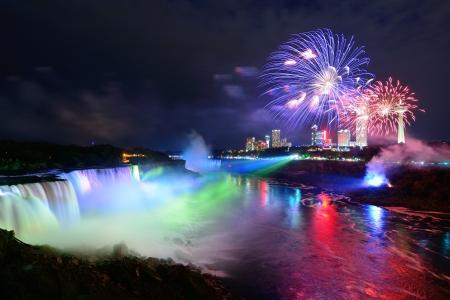 fuegos artificiales: Niagara Falls iluminada de noche por las luces de colores con los fuegos artificiales Foto de archivo